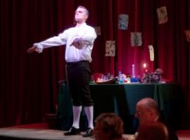 Mann, Arme nach vorn gestreckt, Bühne, roter Vorhang