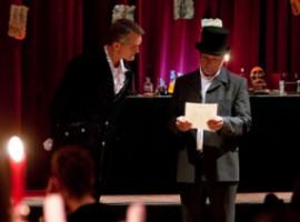 Bühne mit zwei Personen, rechts Mann mit Hut